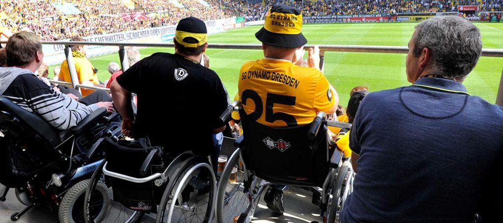 Fans verfolgen im Rollstuhl ein Fußballspiel