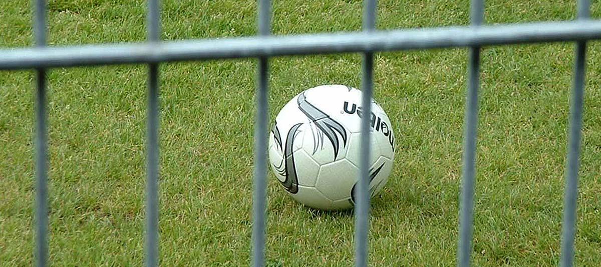 Fußball liegt auf Rasen hinter einem Zaun
